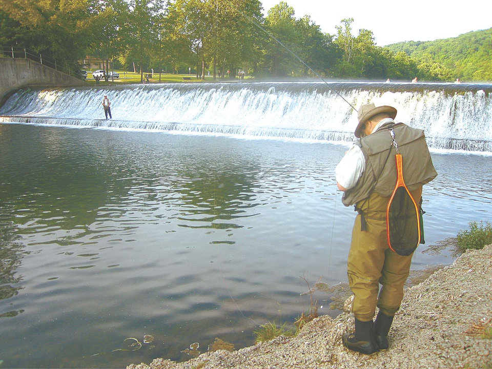 Photo -  Trout like current, and the waterfall at Bennett Spring State Park is a popular place to fish. Bennett Spring State Park is Missouri's most-visited park, and the trout fishing is immensely popular on the spring-fed stream that runs through the park.   PHOTO BY ED GODFREY/THE OKLAHOMAN