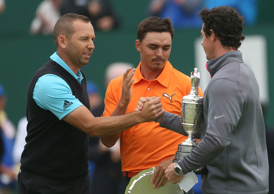 Photo - Rory McIlroy of Northern Ireland holds the Claret Jug trophy after winning the British Open Golf championship and shakes hands with runners up Sergio Garcia of Spain, left, and Rickie Fowler of the US at the Royal Liverpool golf club, Hoylake, England, Sunday July 20, 2014. (AP Photo/Peter Morrison)