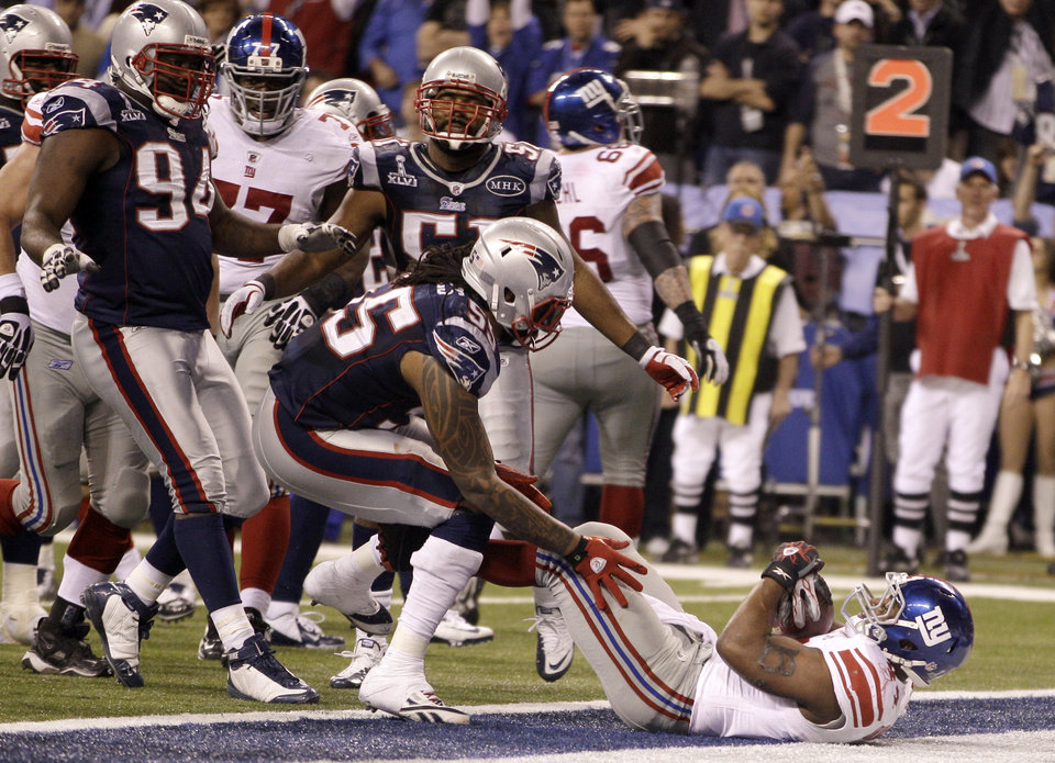 New York Giants running back Ahmad Bradshaw, bottom right, scores a touchdown against New England Patriots linebacker Brandon Spikes during the second half of the NFL Super Bowl XLVI football game, Sunday, Feb. 5, 2012, in Indianapolis. (AP Photo/Matt Slocum) ORG XMIT: SB472