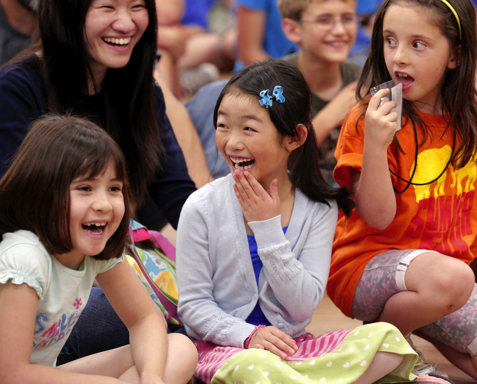 Photo -  Jessie Wong, 6, center, laughs with other children during Physics Fun House at the Norman Public Library. PHOTO BY JIM BECKEL, THE OKLAHOMAN   Jim Beckel -
