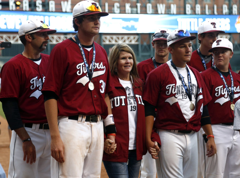 Photo - Kim Tiderman stands with Tuttle as they receive their championship trophies following the class 4A state baseball championship game between Tuttle and Dewey at the Chickasaw Bricktown Ballpark in Oklahoma City, Saturday, May 17, 2014. Photo by Sarah Phipps, The Oklahoman