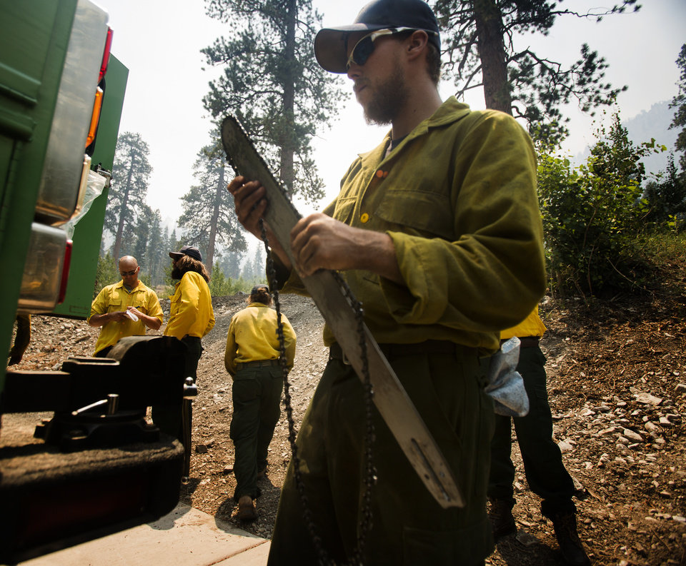 Photo - Andre Sage with the Stanislaus Hotshot Crew cleans a chain saw at Cathedral Rock Picnic Site on Mt. Charleston near Las Vegas after a night on the Carpenter 1 Fire on Tuesday, July 9, 2013. The lightning-caused fire, which started on July 1, has burned nearly 20,000 acres. Over 800 firefighters are working the blaze  in the Spring Mountains National Recreation Area. (AP Photo/Las Vegas Review-Journal, Jeff Scheid)