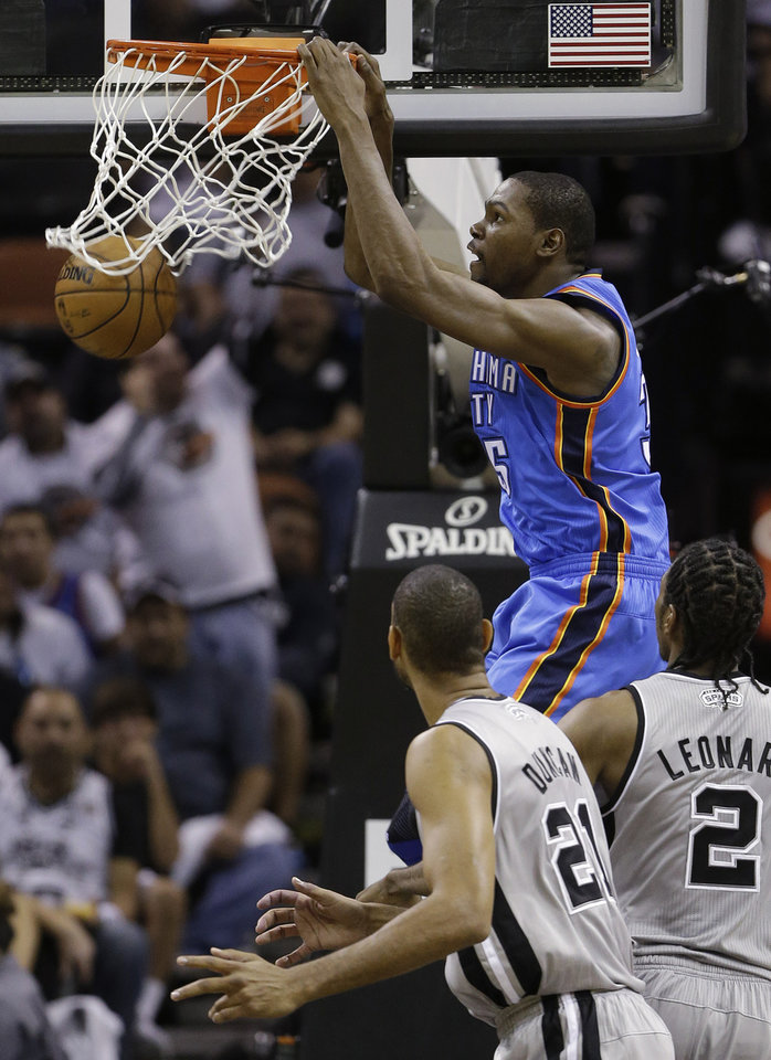 Photo - Oklahoma Thunder's Kevin Durant, center, scores over San antonio Spurs' Tim Duncan (21) and Kawhi Leonard (2) during the second quarter of an NBA basketball game, Thursday, Nov. 1, 2012, in San Antonio. (AP Photo/Eric Gay) ORG XMIT: TXEG106