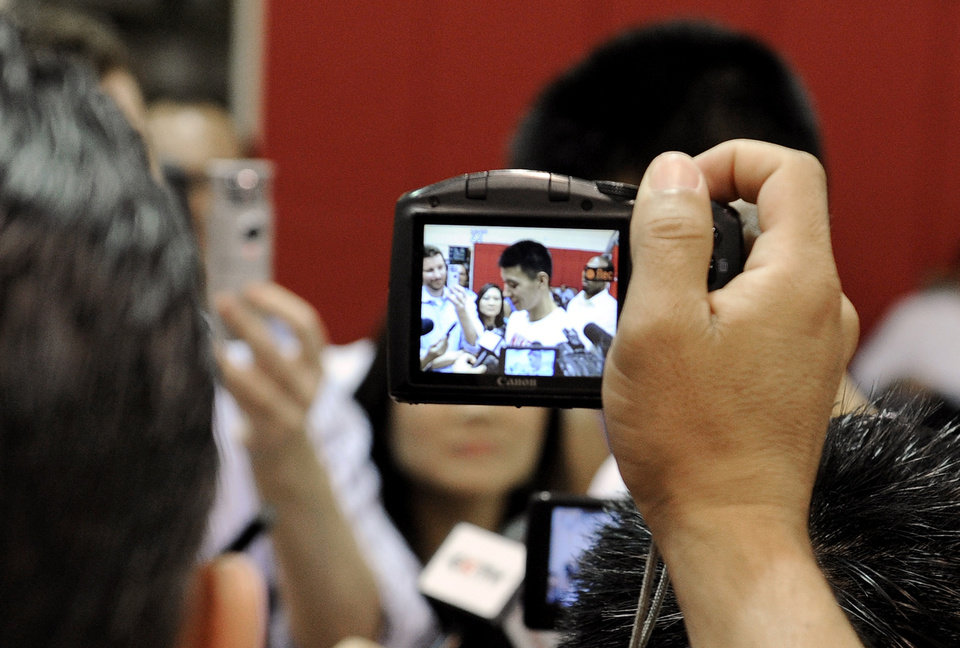 Photo -   A journalist holds up a camera to photograph Houston Rockets' Jeremy Lin as Lin speaks with the media after NBA basketball practice, Tuesday, Sept. 18, 2012, in Houston. (AP Photo/Pat Sullivan)