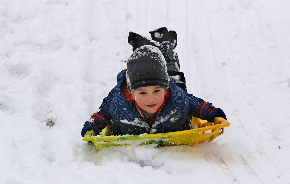 Photo - Bennett sleds down a hill while at the park with their grandmother, Jeanne Hapton, at Bickham Rudkin Park in Edmond, Wednesday, February 5, 2020.  [Photo by Doug Hoke/The Oklahoman]