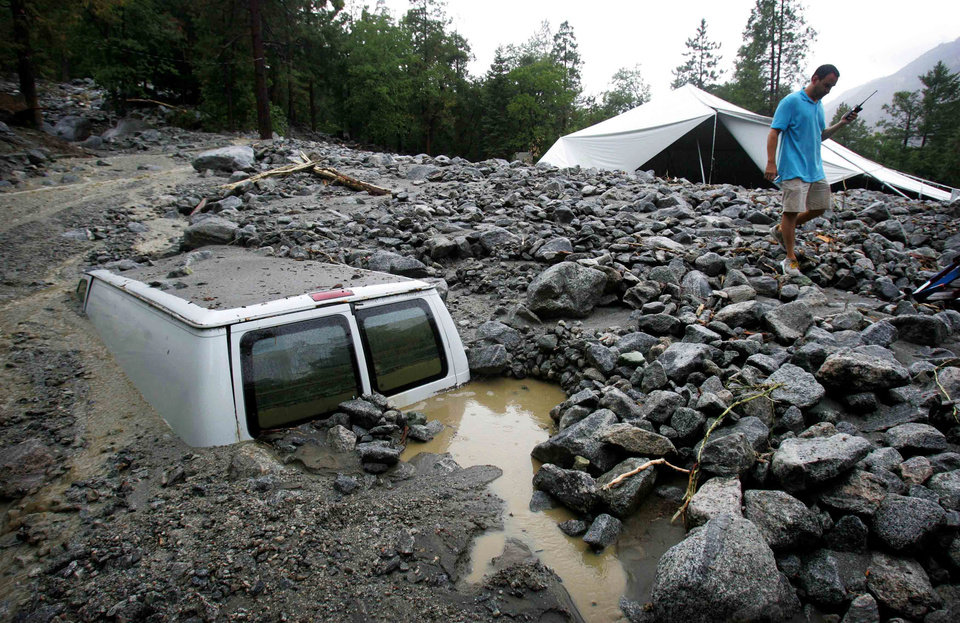 Photo - An official of Forest Home Christian Conference Center in Forest Falls, Calif., inspects damage on the property following thunderstorms on Sunday, Aug. 3, 2014. About 1,500 residents of Oak Glen, and another 1,000 residents of Forest Falls in the San Bernardino Mountains were unable to get out because the roads were covered with mud, rock and debris, authorities said. (AP Photo/The Press-Enterprise, David Bauman)