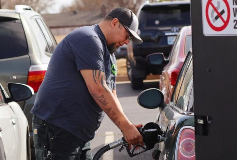 Photo - Mike Salazar prepares to gas up a car. OKC startup company Fueldup has an app where its clients can request someone fill up their car while they're at work or at home. Tuesday, March 3, 2020.  [Photo by Doug Hoke/The Oklahoman]