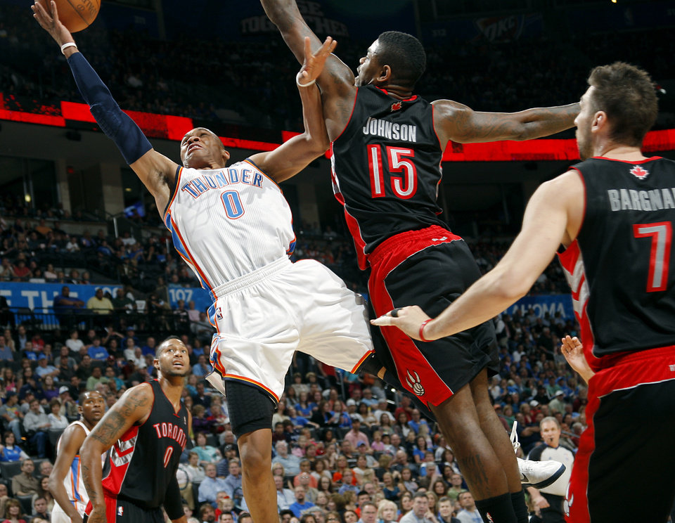 Photo - Oklahoma City's Russell Westbrook puts up a shot in front of Toronto's Amir Johnson during their NBA basketball game at the OKC Arena in downtown Oklahoma City on Sunday, March 20, 2011. Photo by John Clanton, The Oklahoman