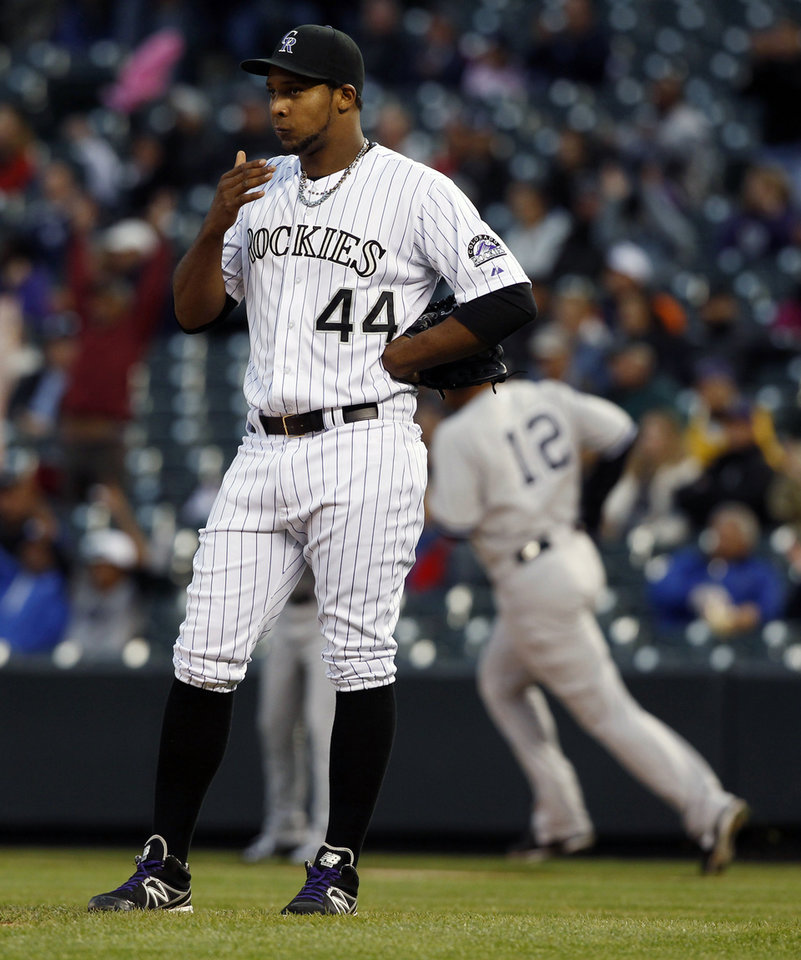 Photo - Colorado Rockies starting pitcher Juan Nicasio, front, reacts as New York Yankees' Vernon Wells, rear, rounds the bases on his two-run home run in the first inning of a baseball game in Denver on Wednesday, May 8, 2013. (AP Photo/David Zalubowski)