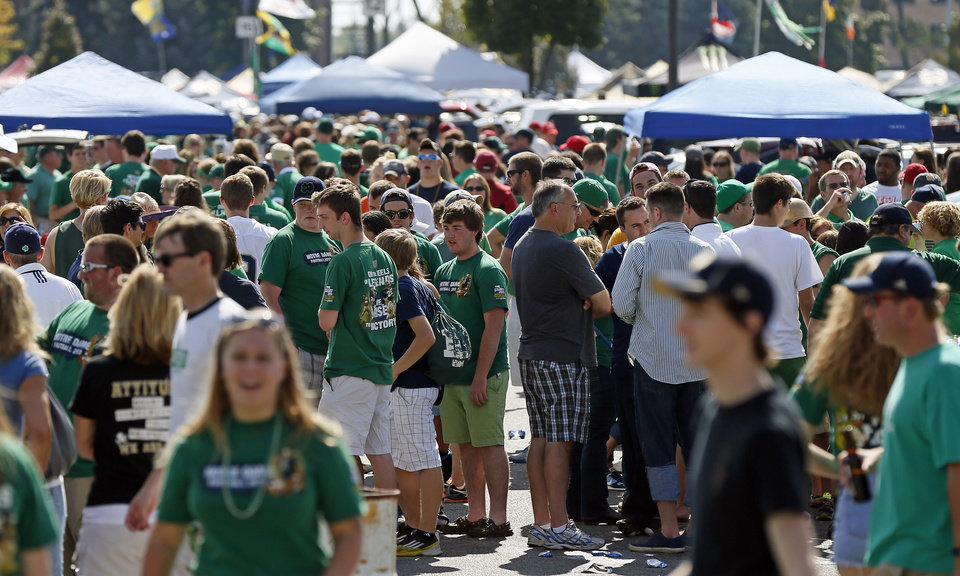 Photo - Thousands of fans fill the stadium parking lot as they tailgate before a college football game between the University of Oklahoma Sooners (OU) and the Notre Dame Fighting Irish at Notre Dame Stadium in South Bend, Ind., Saturday, Sept. 28, 2013. Photo by Nate Billings, The Oklahoman