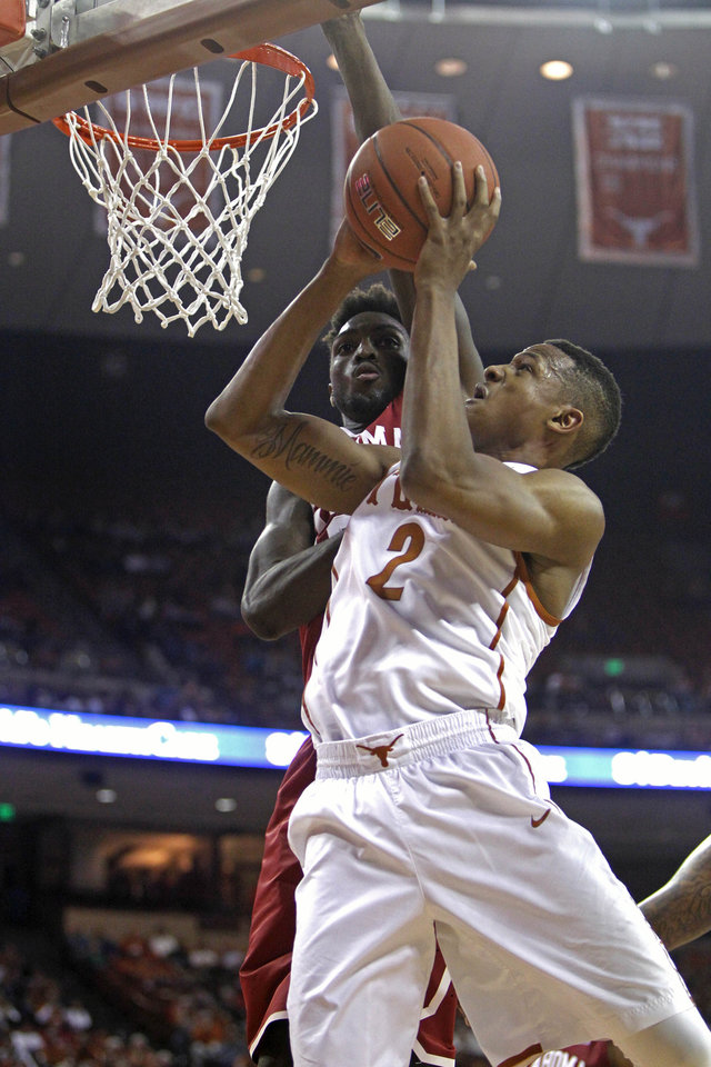 Photo - Texas guard Demarcus Holland (2) puts up a shot against Oklahoma forward Khadeem Lattin during the second half an NCAA college basketball game, Monday, Jan. 5, 2015, in Austin, Texas. Oklahoma won 70-49.  (AP Photo/Michael Thomas)