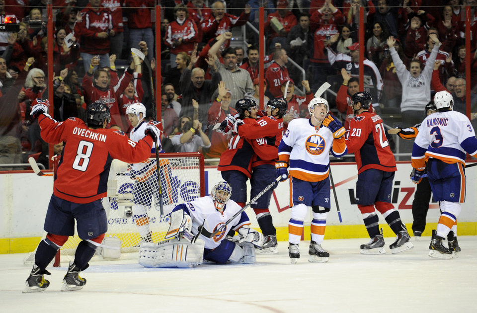 Photo - Washington Capitals center Marcus Johansson (90), of Sweden, celebrates his goal with Nicklas Backstrom (19), also of Sweden, Alex Ovechkin (8), of Russia, and Troy Brouwer (20) as New York Islanders goalie Evgeni Nabokov, center, of Kazakhstan, looks on during the second period an NHL hockey game, Tuesday, Nov. 5, 2013, in Washington. Also seen are New York Islanders center Casey Cizikas (53) and Travis Hamonic (3). (AP Photo/Nick Wass)