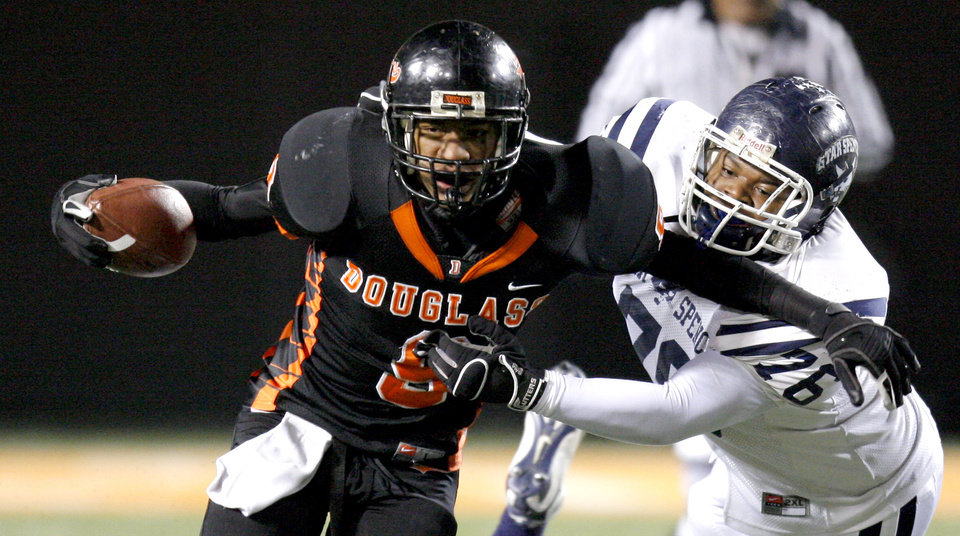 Photo - Marcus Caddell of Douglass runs past Joseph Christian of Star Spencer during the Class 4A high school football state championship game betweeen Star Spencer Douglass at Boone Pickens Stadium in Stillwater, Okla., Saturday, December 5, 2009. Photo by Bryan Terry, The Oklahoman