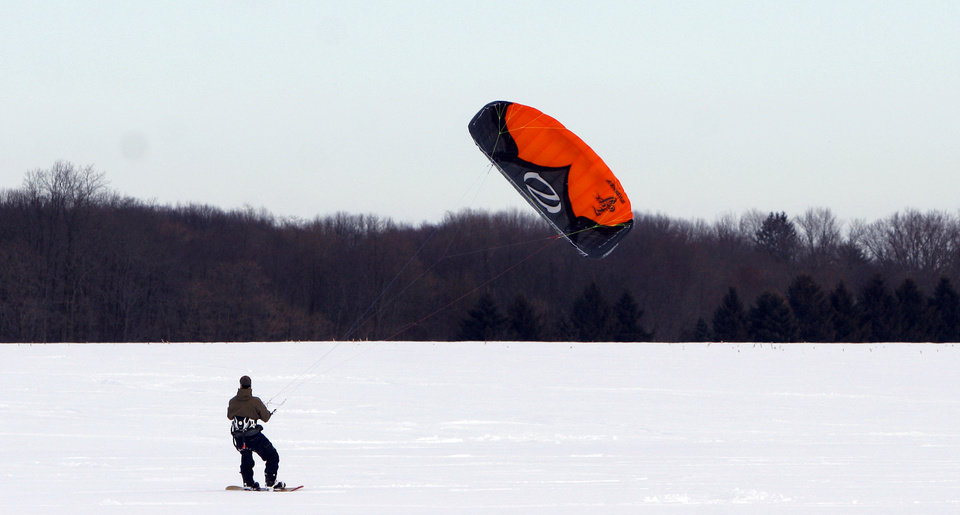 FILE - This Feb. 20, 2010 file photo shows John O'Malley, from Westchester County, N.Y, snowkiting across an open field in Cranbury, N.J.  Visitors to winter recreation destinations enjoy activities like airboarding, snowkiting and skijoring as alternatives to more traditional snow sports such as skiing or snowboarding.   (AP Photo/Jim Gerberich, file)
