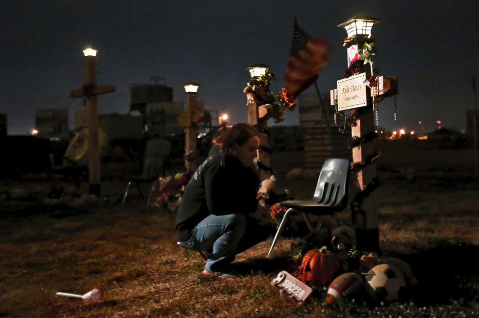 Mikki Davis kneels at the cross for her son Kyle during a candle light vigil at the Plaza Towers Elementary grounds in Moore, Okla. on Wednesday, Nov. 20, 2013. Family and friends gathered for a six month memorial of the May 20th tornado that killed seven student at the school.  Photo by Chris Landsberger, The Oklahoman