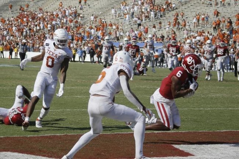 Photo -  Oklahoma's Tre Brown (6) intercepts a pass in front of Texas' Tarik Black (0) in the fourth overtime to seal the Sooners 53-45 win over the Longhorns at the Cotton Bowl in Dallas. [Bryan Terry/The Oklahoman]