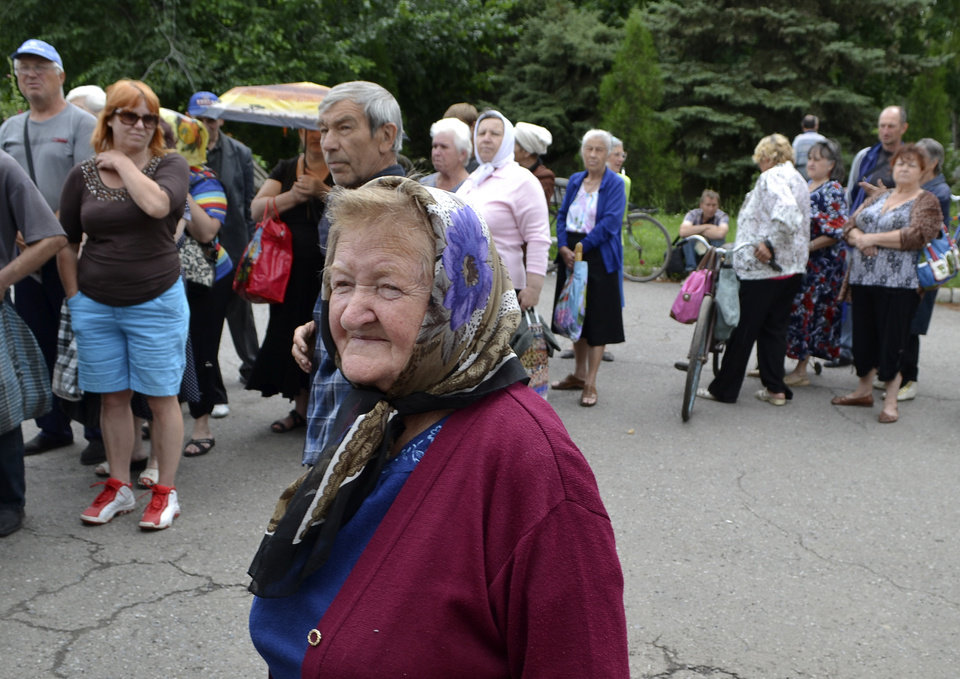 Photo - Local citizens lineup to get free food in besieged Slovyansk, eastern Ukraine, Monday, June 23, 2014. Insurgents promised Monday to honor a cease-fire declared by the Ukrainian president and engage in more talks to help resolve the conflict that has left hundreds dead in eastern Ukraine.(AP Photo/Andrei Petrov)