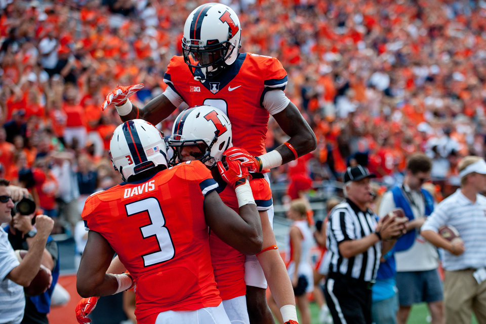 Photo - Illinois tight end Jon Davis (3) is congratulated by teammate Matt LaCosse (11) and  wide receiver Geronimo Allison (8), top, after scoring a touchdown during the second quarter of an NCAA college football game against Youngstown State, Saturday, Aug. 30, 2014, at Memorial Stadium in Champaign, Ill. (AP Photo/Bradley Leeb)