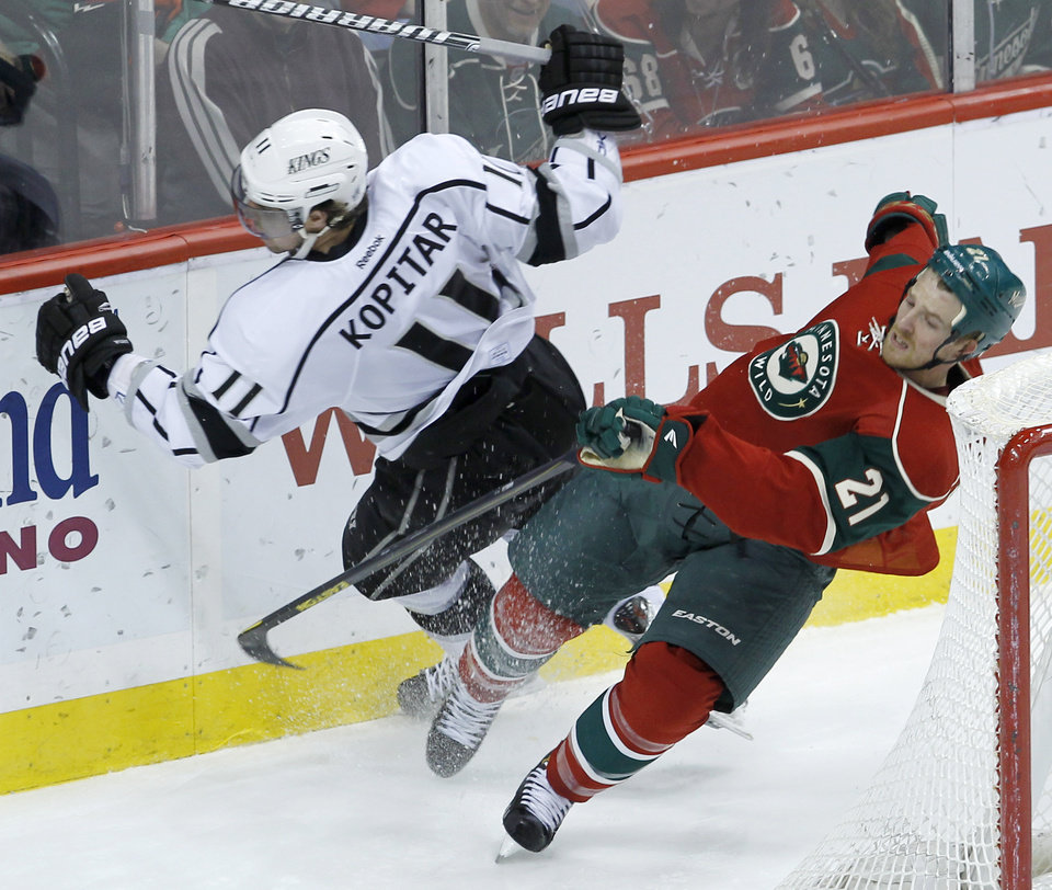 Photo - Minnesota Wild center Kyle Brodziak (21) slams into Los Angeles Kings center Anze Kopitar (11), of Yugoslavia, during the third period of an NHL hockey game in St. Paul, Minn., Tuesday, April 23, 2013. The Wild beat the Kings 2-1.(AP Photo/Ann Heisenfelt)