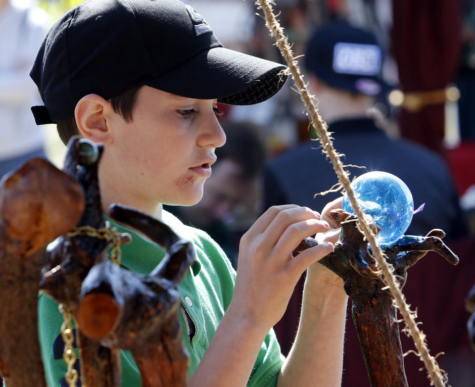 Levi Rollf, Ninnekah sixth grade student, looks at a glass orb on a staff during the Medieval Fair at Reaves Park on Friday, April 5, 2013 in Norman, Okla.  Photo by Steve Sisney, The Oklahoman