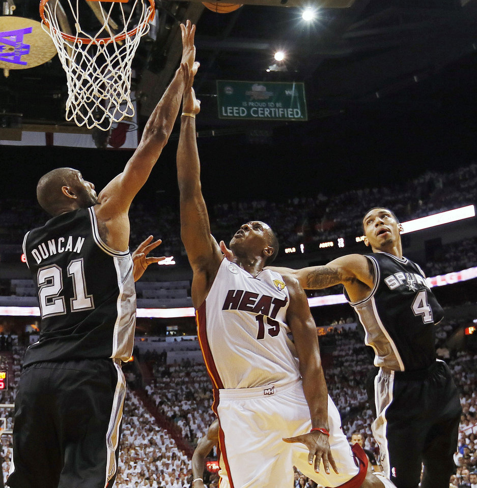 Photo - Miami Heat point guard Mario Chalmers (15) shoots against San Antonio Spurs power forward Tim Duncan (21) and San Antonio Spurs shooting guard Danny Green (4) during the first half of Game 2 of the NBA Finals basketball game, Sunday, June 9, 2013 in Miami. (AP Photo/Christian Petersen, Pool)