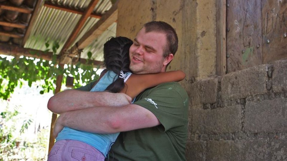 Photo -  James McGovern embracing his sponsored child from Nicaragua, Alejandra, during their first interaction. [FEED THE CHILDREN]