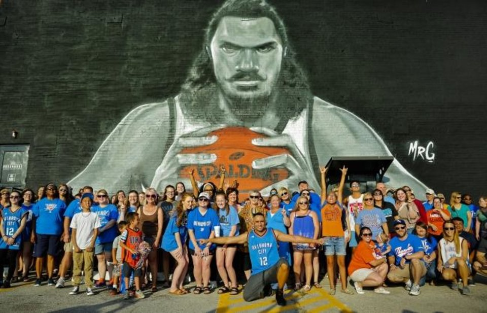 Photo -  Thunder fans pose for a photo four years ago in front of the mural of Thunder center Steven Adams painted on the side of the Paramount building by artist Graham Hoete. [Chris Landsberger/The Oklahoman]