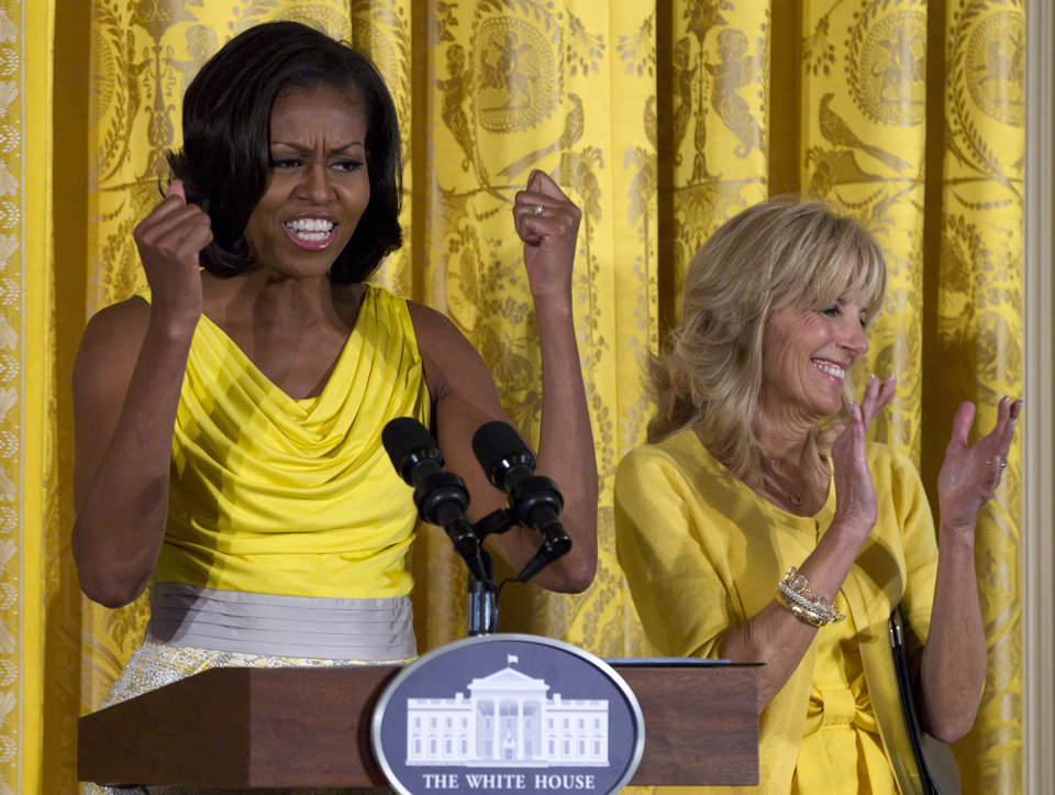 Photo - FILE - In this May 10, 2012, file photo, first lady Michelle Obama, accompanied by Jill Biden speaks at a Joining Forces event in honor of military mothers in the East Room of the White House in Washington. Michelle Obama has a new look, both in person and online, and with the president's re-election, she has four more years as first lady, too. The first lady is trying to figure out what comes next for this self-described