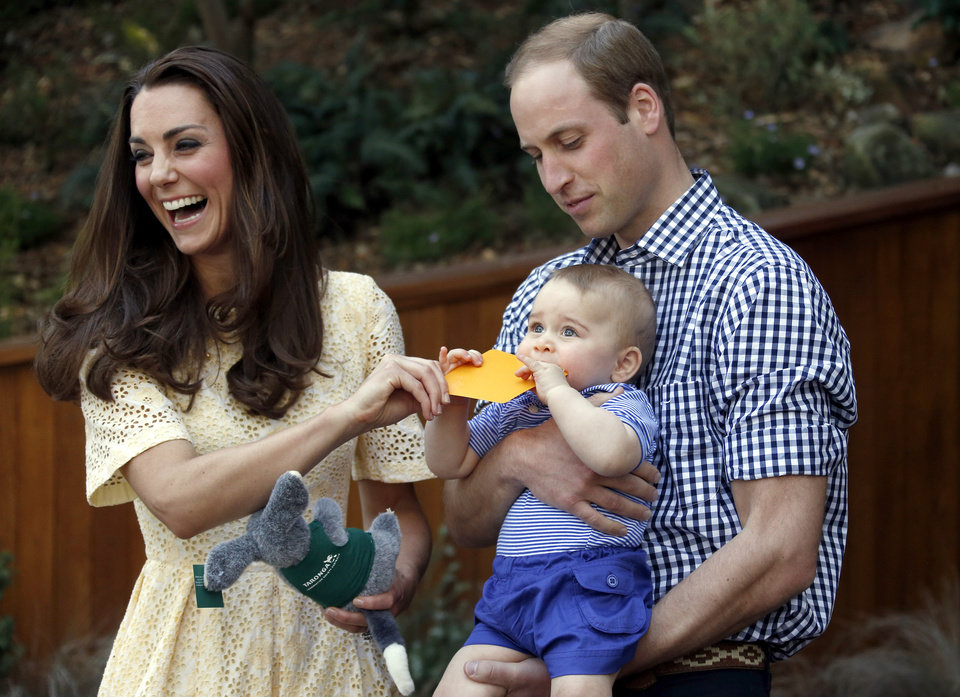 Photo - Britain's Kate, the Duchess of Cambridge, and her husband Prince William react as their son Prince George bites a small present that was given to him during a visit to Sydney's Taronga Zoo, Australia Sunday, April 20, 2014.  (AP Photo/David Gray, Pool)
