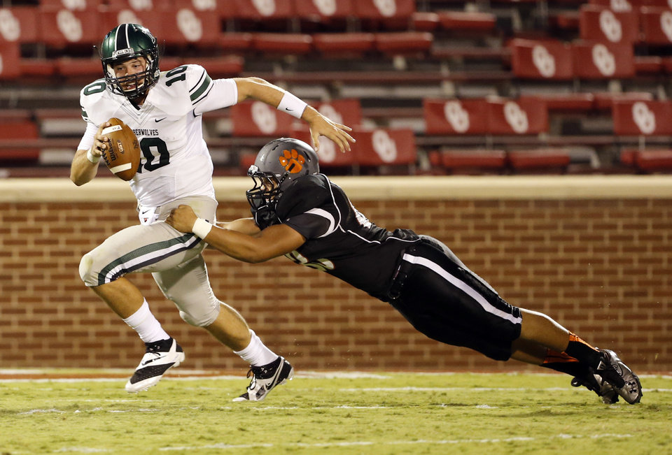 Photo - Norman's High's Cade Parker tackles Norman North's quarterback David Cornwell (10) for a loss in the second quarter at Gaylord Family-Oklahoma Memorial Stadium in Norman, Okla., on Thursday, Sept. 5, 2013. Photo by Steve Sisney, The Oklahoman