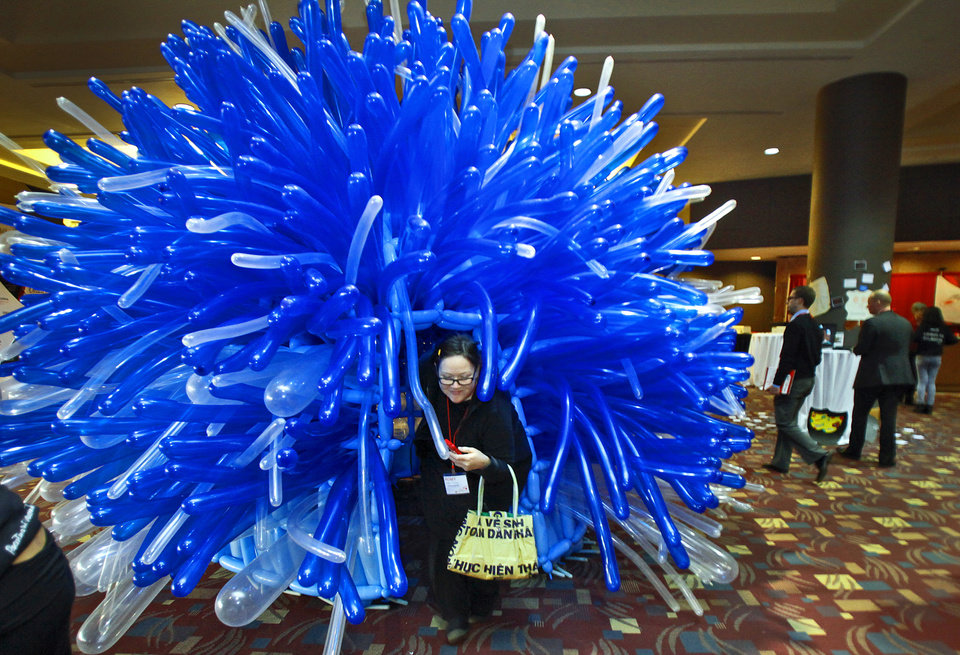 Photo - Romy Owens climbs out of a balloon sculpture on display at the Creativity World Forum at the Cox Convention Center on Wednesday, Nov. 17, 2010, in Oklahoma City, Okla.  Photo by Chris Landsberger, The Oklahoman