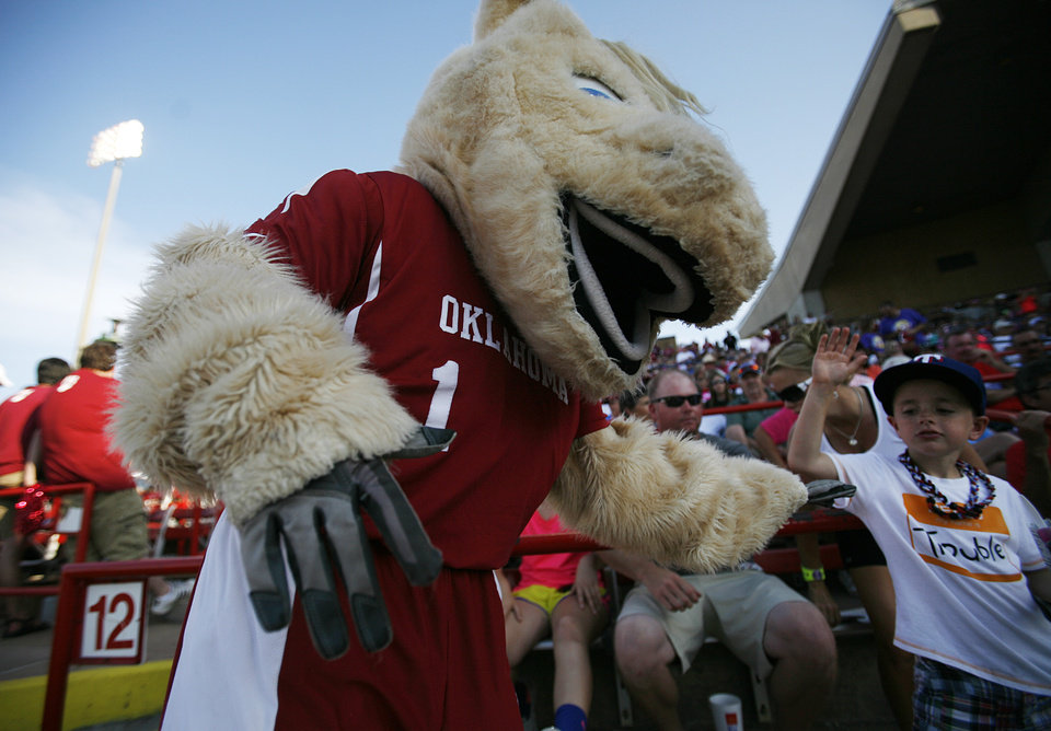 OU mascot, Sooner, high-fives Blake Beste, 8, of Texas, during a Women's College World Series game between OU and Alabama at ASA Hall of Fame Stadium in Oklahoma City, Monday, June 4, 2012.  Photo by Garett Fisbeck, The Oklahoman
