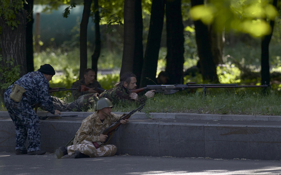 Photo - Pro-Russian insurgents aim their rifles during fighting around the airport outside Donetsk, Ukraine, Monday, May 26, 2014. Ukraine's military launched air strikes Monday against the separatists who had taken over the airport in the eastern city of Donetsk, suggesting that fighting in the east is far from over. (AP Photo/Vadim Ghirda)