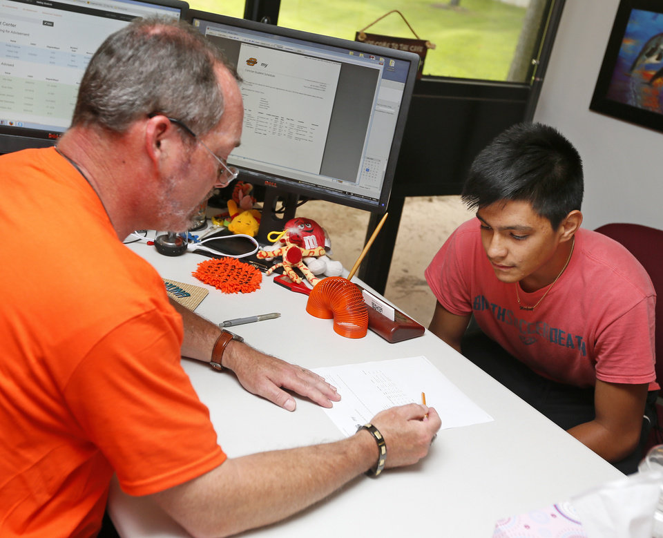 Photo -  Academic adviser James Anderson helps freshman Rafael Ulloa, 18, with his class schedule at Oklahoma State University-Oklahoma City. [Photo by Nate Billings, The Oklahoman]