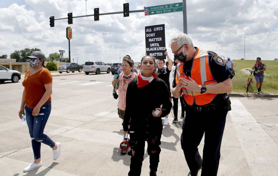 Photo - A Norman Police Officer talks with organizer Lirey Munoz as protesters march to the Norman Police Department in Norman, Okla.  Tuesday, June 2, 2020.  [Sarah Phipps/The Oklahoman]