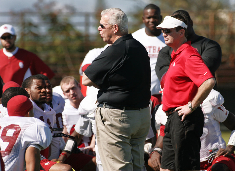 Photo - Bill Parcells, center, Miami Dolphins executive vice president of football operations, gives a pep talk to Oklahoma players as coach Bob Stoops looks on during practice on Saturday. AP Photo
