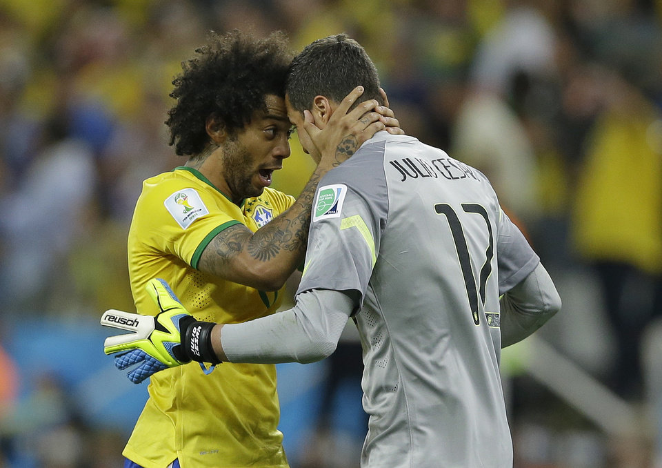 Photo - Brazil's goalkeeper Julio Cesar celebrates with Marcelo after Oscar scored the 3rd goal during the group A World Cup soccer match between Brazil and Croatia, the opening game of the tournament, in the Itaquerao Stadium in Sao Paulo, Brazil, Thursday, June 12, 2014. (AP Photo/Kirsty Wigglesworth)