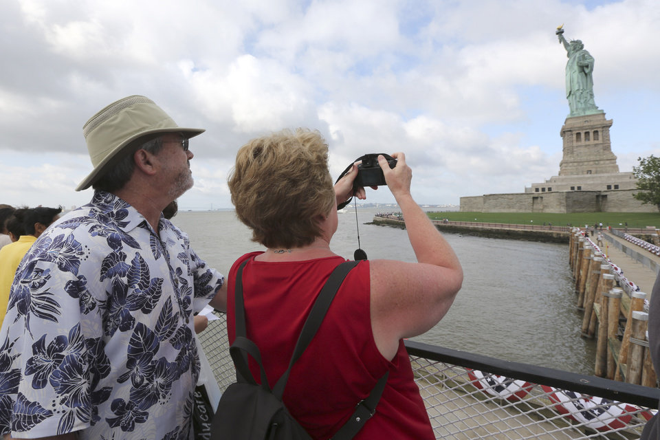 Photo - Rodney and Judy Long, of Charlotte, N.C., take a photo of the Statue of Liberty as they arrive on the first tourist ferry to leave Manhattan, Thursday, July 4, 2013, in New York. The Statue of Liberty finally reopened on the Fourth of July months after Superstorm Sandy swamped its island in New York Harbor as Americans across the country marked the holiday with fireworks and barbecues. (AP Photo/Mary Altaffer)