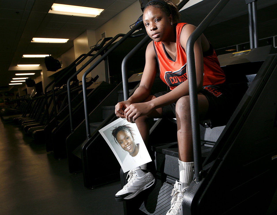 Photo - Holding a picture of herself from her freshman year of college, Oklahoma State University women's college basketball player Shaunte Smith poses in the exercise room at Gallagher-Iba Arena in Stillwater on Tuesday, Dec. 30, 2008. By John Clanton, The Oklahoman ORG XMIT: KOD