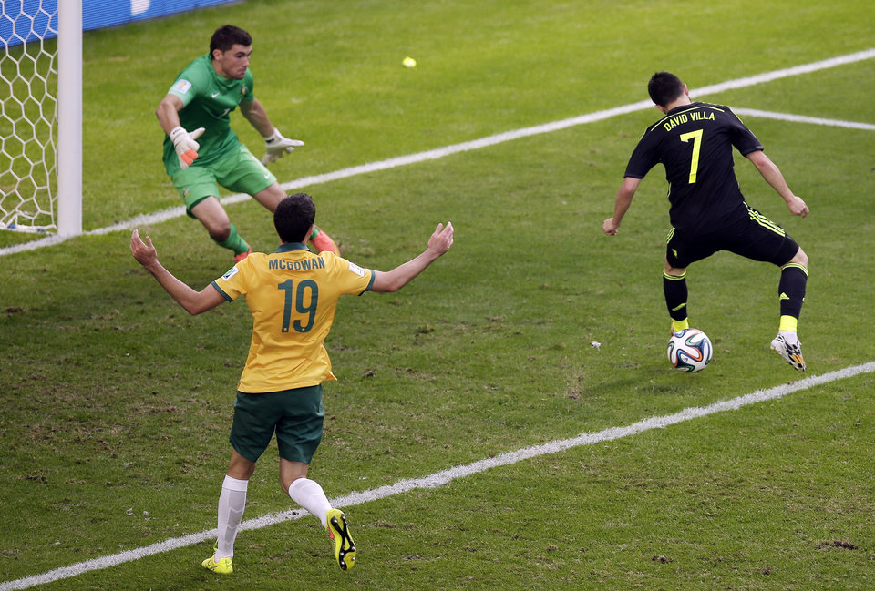 Photo - Spain's David Villa, right, scores his side's first goal during the group B World Cup soccer match between Australia and Spain at the Arena da Baixada in Curitiba, Brazil, Monday, June 23, 2014. (AP Photo/Michael Sohn)