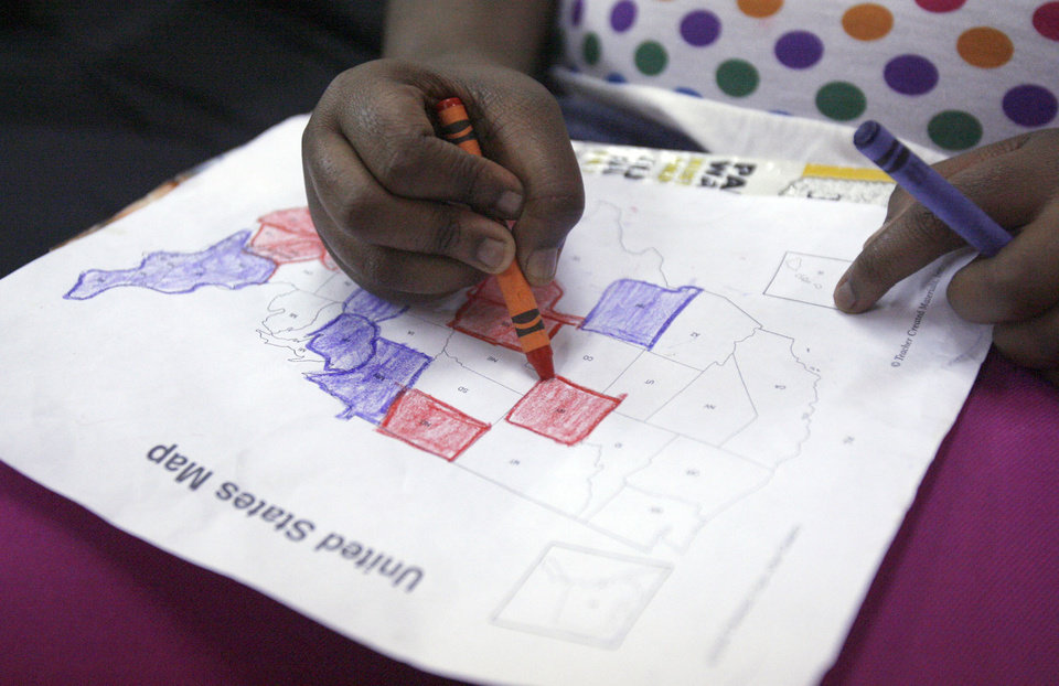 Photo - Nicalet Broom, 10, of Oklahoma City colors a presidential map as she watches election coverage at a watch party for Barack Obama at the Images of Hair and Nails  salon Tuesday, Nov .4, 2008, in Oklahoma City. PHOTO BY SARAH PHIPPS, THE OKLAHOMAN.