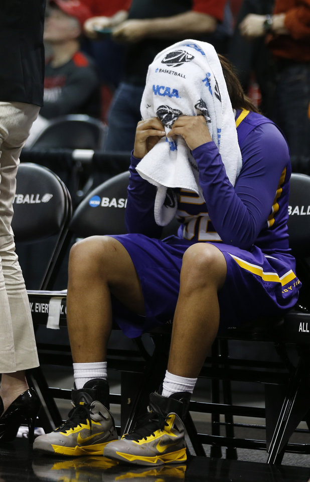 Photo - LSU guard Danielle Ballard (32) covered her head with a towel in the final moments of their 73-47 loss to Louisville in a regional semi final game at the NCAA college basketball tournament, Sunday, March 30, 2014, in Louisville, Ky.  (AP Photo/John Bazemore)