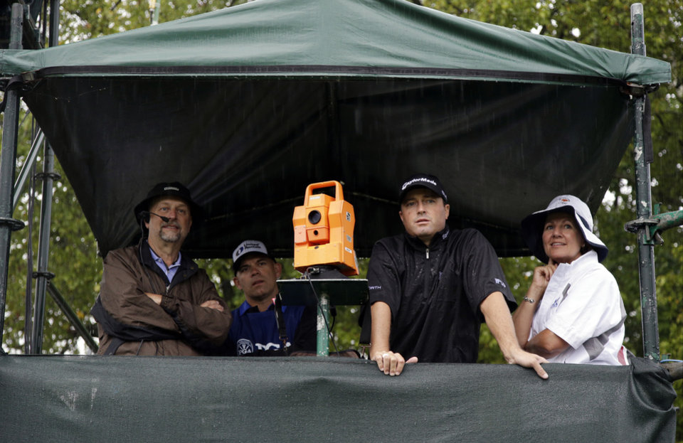 Photo - Ryan Palmer, second from right, hides from the rain in a tower on the first hole during the second round of the PGA Championship golf tournament at Valhalla Golf Club on Friday, Aug. 8, 2014, in Louisville, Ky. (AP Photo/John Locher)