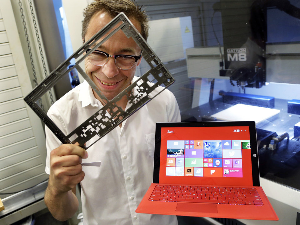 Photo - In this photo taken July 3, 2014, Ralf Groene, chief designer for the Microsoft Surface tablet computer, poses for a photo with a Surface 3 Pro tablet, right, in front of a milling machine used to produce parts for the computer, like the one he is holding at left, in Redmond, Wash. As Microsoft competes with Apple and other companies for hardware sales, the software giant has put a new emphasis on design. (AP Photo/Ted S. Warren)