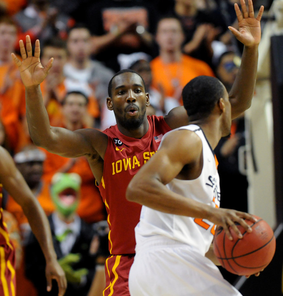 Photo - Iowa State guard DeAndre Kane, left, defends against Oklahoma State guard Markel Brown, right, during an NCAA college basketball game in Stillwater, Okla., Monday, Feb. 3, 2014. Kane scored 26 points in the 98-97 win over Oklahoma State. (AP Photo/Brody Schmidt)