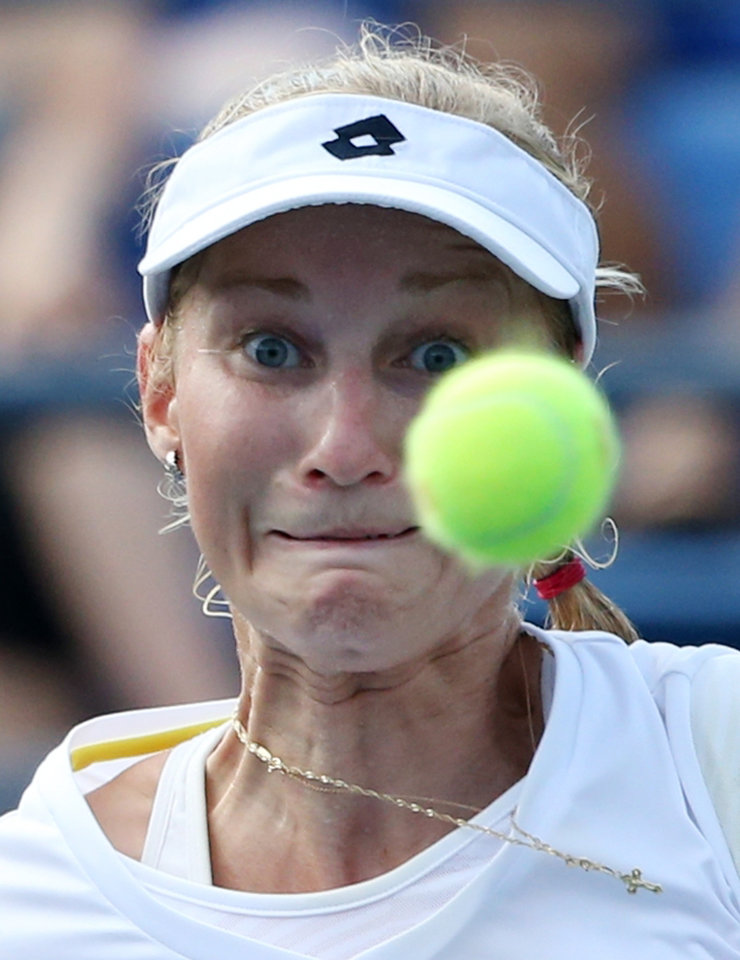 Photo - Ekaterina Makarova, of Russia, returns a shot against Eugenie Bouchard, of Canada,  during the fourth round of the 2014 U.S. Open tennis tournament, Monday, Sept. 1, 2014, in New York. (AP Photo/John Minchillo)