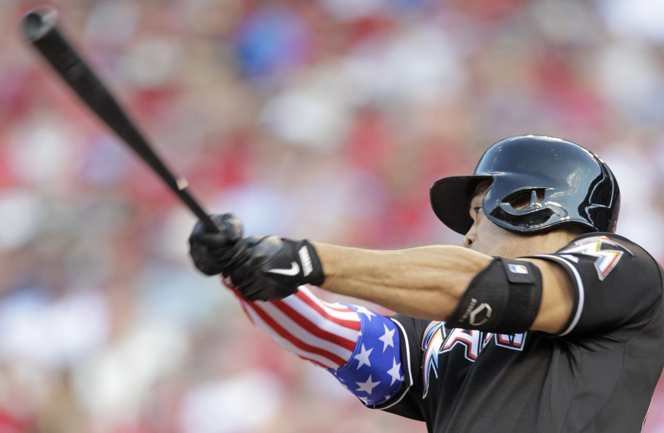 Photo - Miami Marlins' Giancarlo Stanton wears a stars and stripes sleeve as he bats in the first inning of a baseball game against the St. Louis Cardinals, Friday, July 4, 2014, in St. Louis.(AP Photo/Tom Gannam)