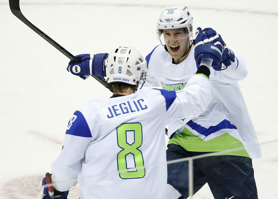 Photo - Slovenia forward Robert Sabolic (55) celebrates with Slovenia forward Ziga Jeglic after a second period goal against Russia during a men's ice hockey game at the 2014 Winter Olympics, Thursday, Feb. 13, 2014, in Sochi, Russia. (AP Photo/Mark Humphrey)