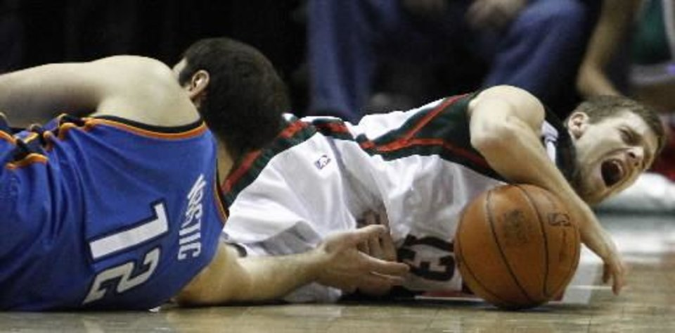Oklahoma City Thunder\'s Nenad Krstic (12) fouls Milwaukee Bucks\' Luke Ridnour (13) as they go after a loose ball during the overtime of an NBA basketball game Saturday, Jan. 2, 2010, in Milwaukee. The Bucks won 103-97 in overtime. (AP Photo/Morry Gash)