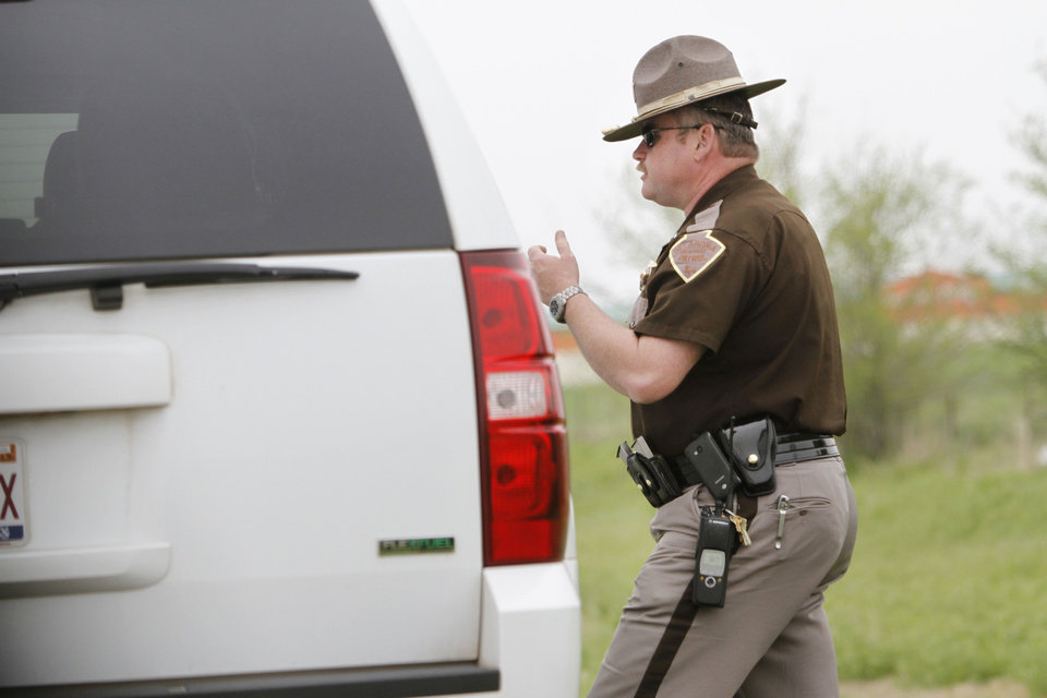 Photo - Lt. Mark Reynolds, with the Oklahoma Highway Patrol, gives a warning to a motorist who was following too closely April 16 on Interstate 40 in Oklahoma City. Photos By Steve Gooch, The Oklahoman